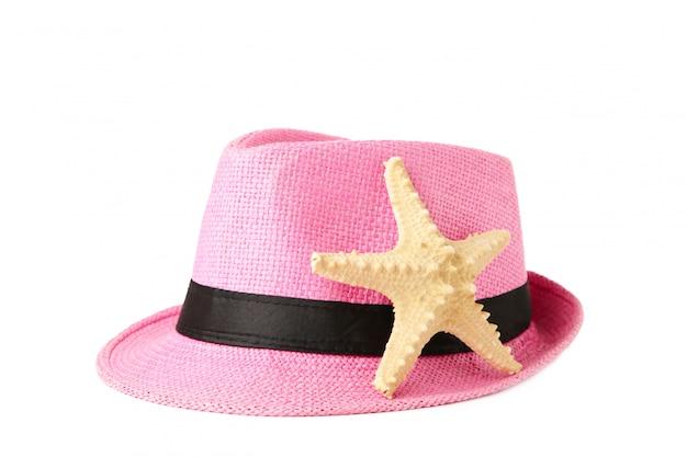 Cappello rosa e stelle marine isolati su fondo bianco.