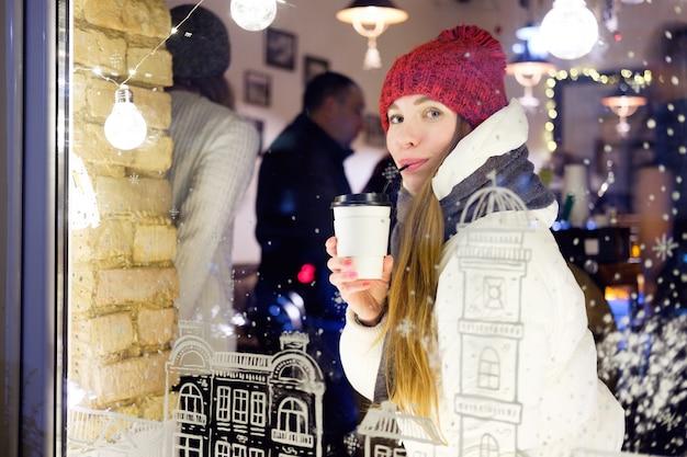 Cappello rosso indossato ragazza e giacca bianca che si siedono in caffè