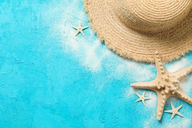 Cappello, sabbia e stelle marine di paglia sul fondo di colore, spazio per testo. concetto di vacanze estive