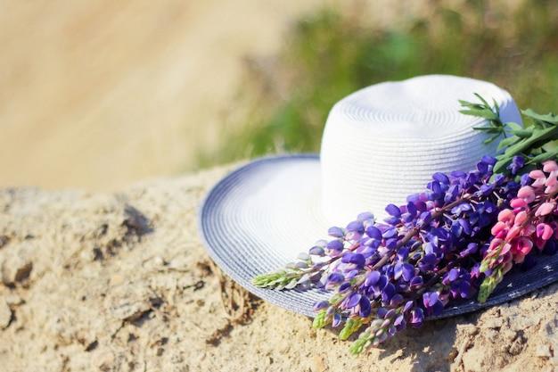 Cappello vicino a un mazzo di fiori di lupino. picnic estivi di concetto. cappello decorato con fiori bouquet.