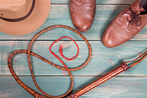 Cappello vintage della fedora, bullwhip e vecchie scarpe marroni sulla tavola di legno verde