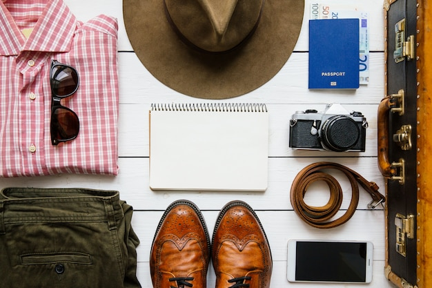 Cappello vintage hipster e accessori da viaggio in valigia sul tavolo di legno bianco prima dell'imballaggio