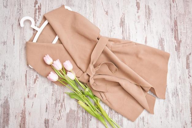 Cappotto beige con cintura e tulipani rosa