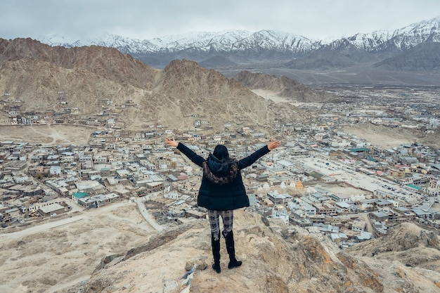 Cappotto d'uso del giovane viaggiatore asiatico della donna che gode della vista della città di leh ladakh in leh, ladakh, india.