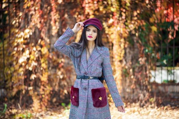 Cappotto e cappuccio d'uso di inverno della giovane bella ragazza nel fondo delle foglie di autunno.