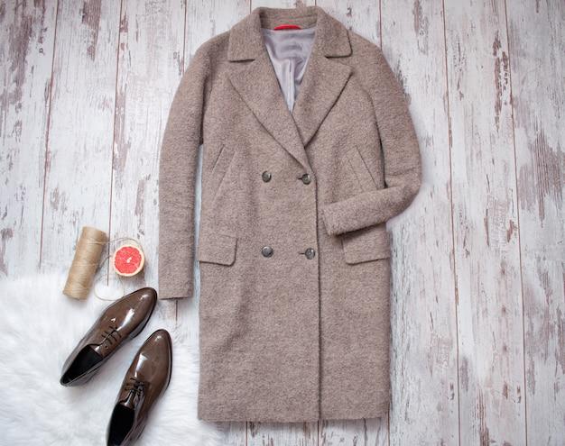 Cappotto marrone e scarpe di vernice marrone su una pelliccia bianca, pompelmo e spago