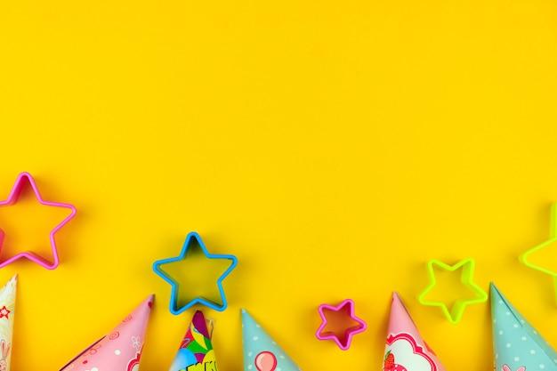Cappucci, pallone e stelle della festa di compleanno su fondo giallo con copyspace