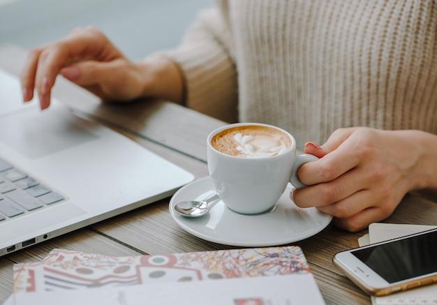 Cappuccino caldo con il portatile sul tavolo