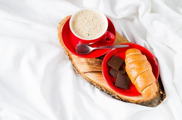 Cappuccino, cioccolato e croissant su un letto.