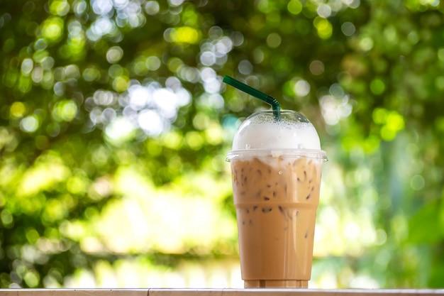 Cappuccino di ghiaccio in tazza plastice. take away package. bevanda con il backgr del bokeh verde della natura