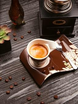 Cappuccino di latteo schiumoso, latte in tazza decorativa e piatto marrone con cucchiaio metallico.