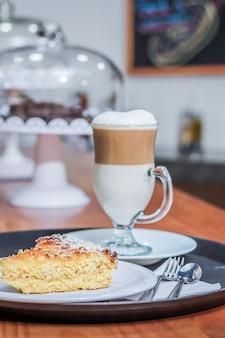 Cappuccino e un pezzo di torta su un vassoio da ristorante.