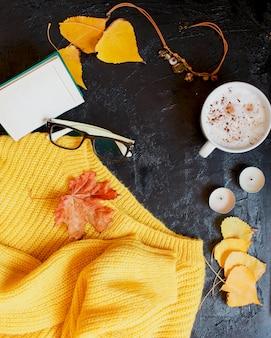 Cappuccino, occhiali e un maglione giallo brillante giacciono sul buio