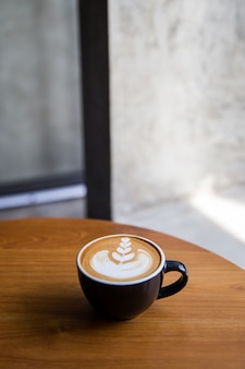 Cappuccino saporito con bella arte del latte sulla tavola di legno nel caffè.