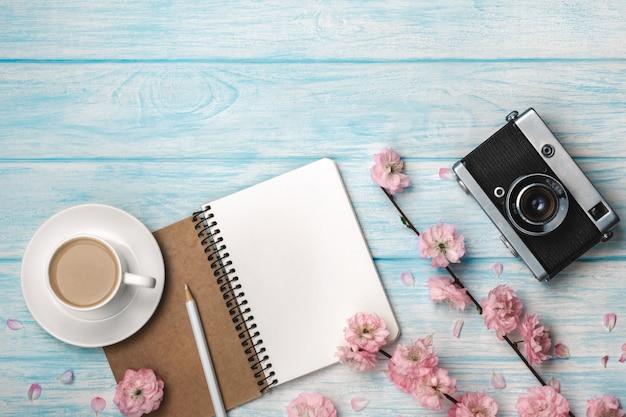 Cappuccino tazza bianca con fiori di sakura, notebook e vecchia macchina fotografica su una tavola di legno blu