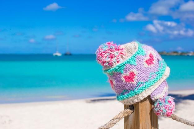 Cappuccio tricottato caldo del primo piano sul recinto alla spiaggia tropicale