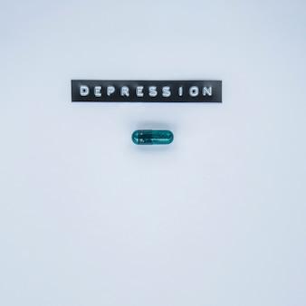Capsula verde con etichetta di depressione su sfondo grigio