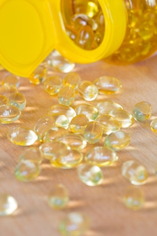 Capsule del gel di omega 3 dell'olio di fegato di merluzzo isolate su fondo di legno