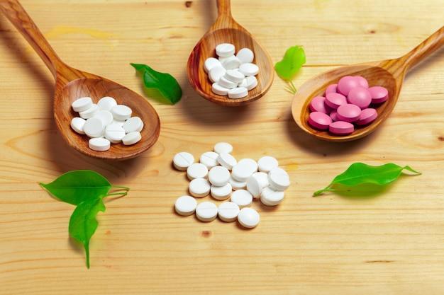 Capsule della medicina, pillole sul cucchiaio di legno