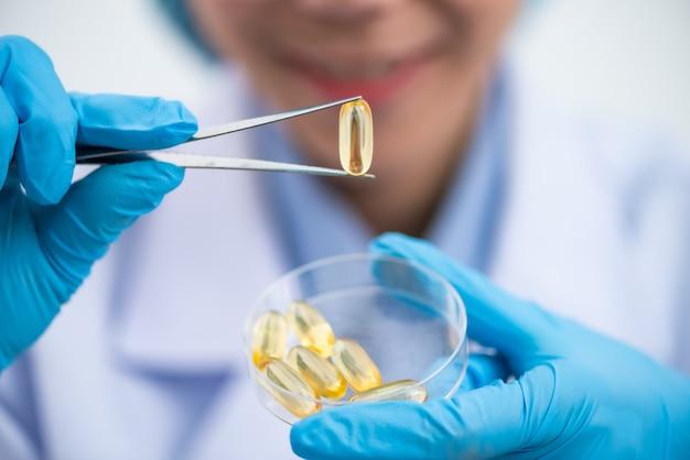 Capsule di olio di pesce con omega 3 e vitamina d in una bottiglia di vetro su struttura di legno