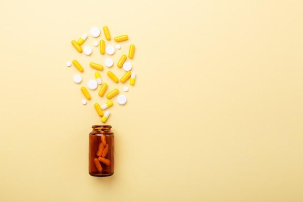Capsule e pillole multicolori capsule da bottiglia di vetro sul giallo