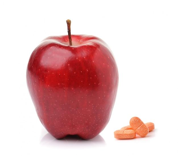 Capsule mature rosse delle pillole e della mela isolate su bianco