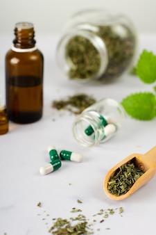 Capsule mediche del primo piano con le erbe sulla tavola