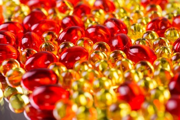 Capsule mediche gialle e rosse su una superficie a specchio
