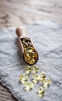 Capsule omega-3 nella paletta di legno