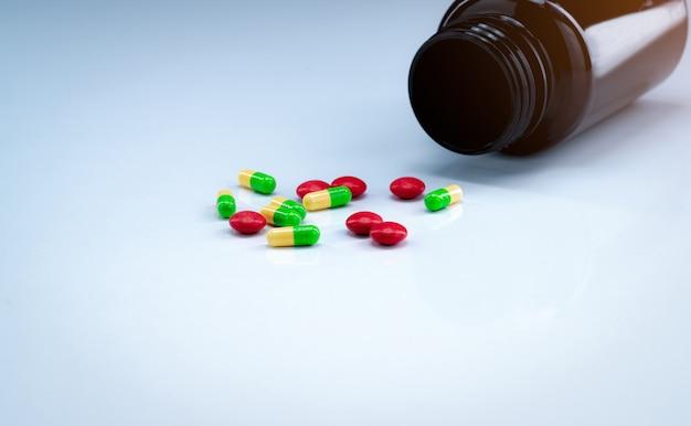Capsule verdi e gialle con le pillole rosse delle compresse vicino alla bottiglia marrone della droga su fondo bianco. industria farmaceutica. antidolorifico.