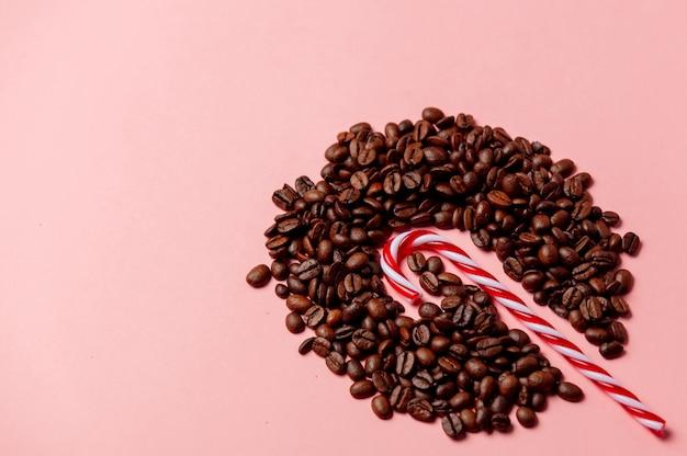 Caramella di natale e chicchi di caffè sulla parete rosa