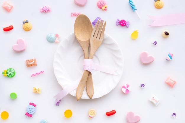 Caramella dolce con il cucchiaio e forchetta su fondo bianco, fondo di giorno di biglietti di s. valentino.