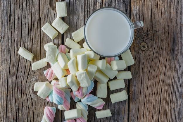 Caramella gommosa e molle colorata con latte sulla tavola di legno