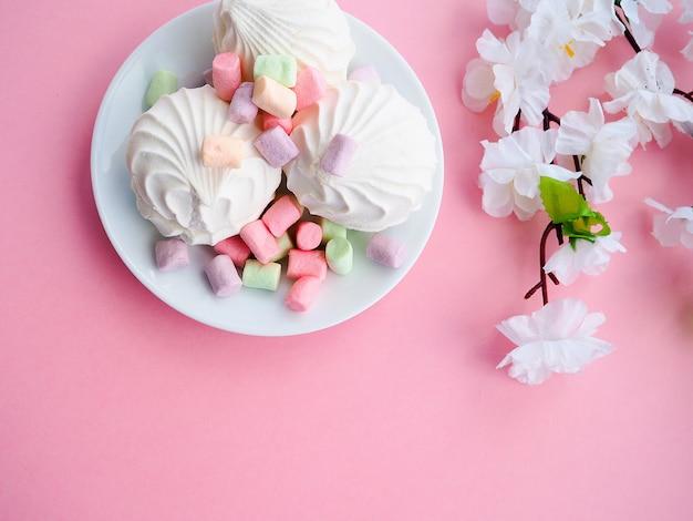 Caramella gommosa e molle in zolla bianca sul colore rosa