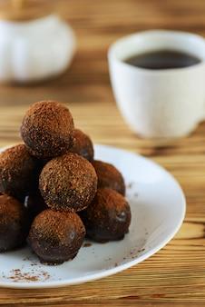 Caramelle al cioccolato a forma di piramide con una tazza di caffè su un tavolo di legno.