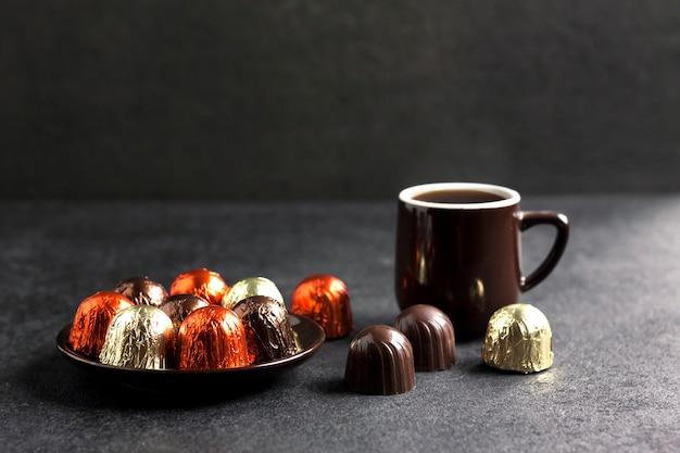 Caramelle al cioccolato avvolte in un foglio multicolore e tazza di caffè