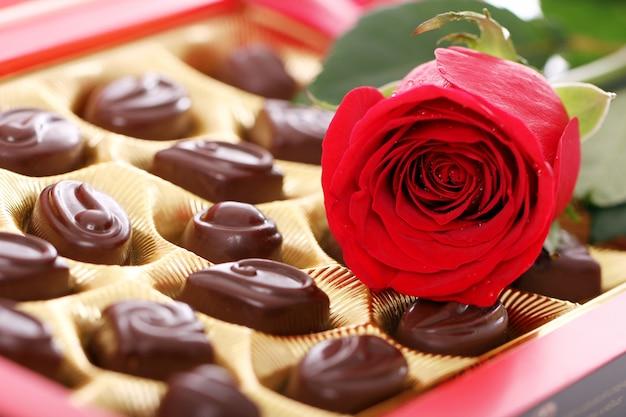 Caramelle al cioccolato e rose rosse