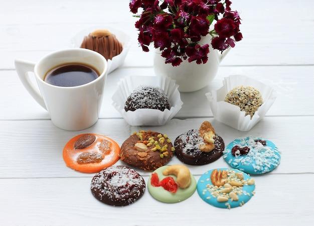 Caramelle al cioccolato, una tazza di caffè e un mazzo di fiori per san valentino su legno