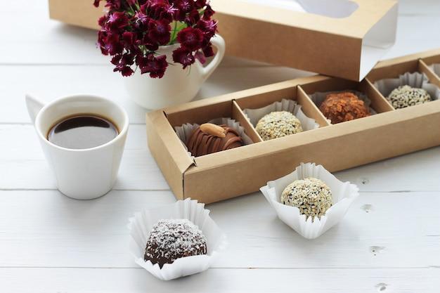 Caramelle al cioccolato, una tazza di caffè e un mazzo di fiori per san valentino sul tavolo di legno.