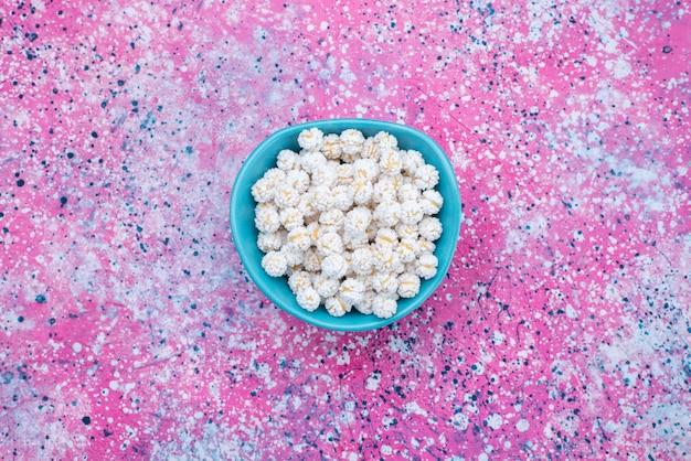 Caramelle bianche di vista dall'alto all'interno del piatto blu sul colore della caramella viola della caramella