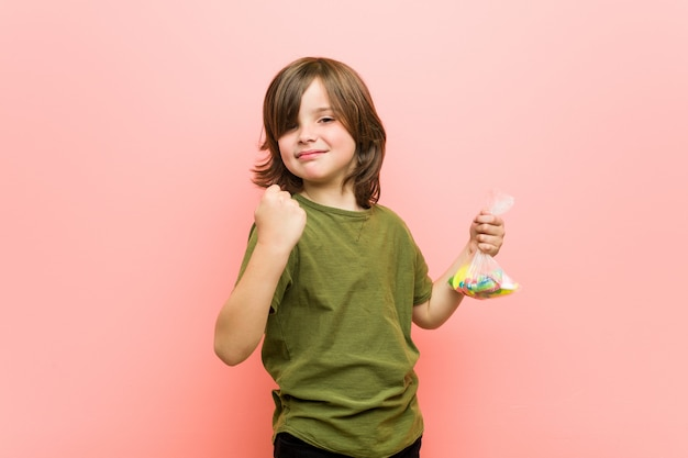 Caramelle caucasiche della tenuta del ragazzino che mostrano pugno alla macchina fotografica, espressione facciale aggressiva.