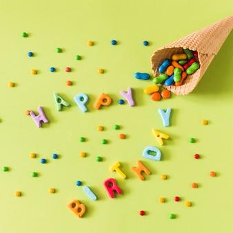 Caramelle che si rovesciano dal cono gelato della cialda sul buon compleanno sopra la superficie di verde