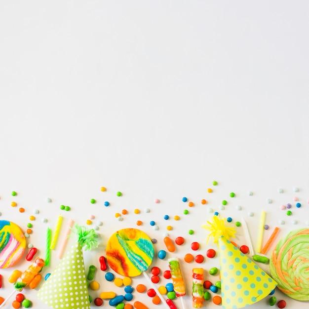 Caramelle colorate; candele e cappello del partito su sfondo bianco