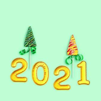 Caramelle colorate creative per capodanno o natale. lecca-lecca a forma di albero di natale e figura gonfiabile dorata metallica 2021 su sfondo di carta colorata neo menta.