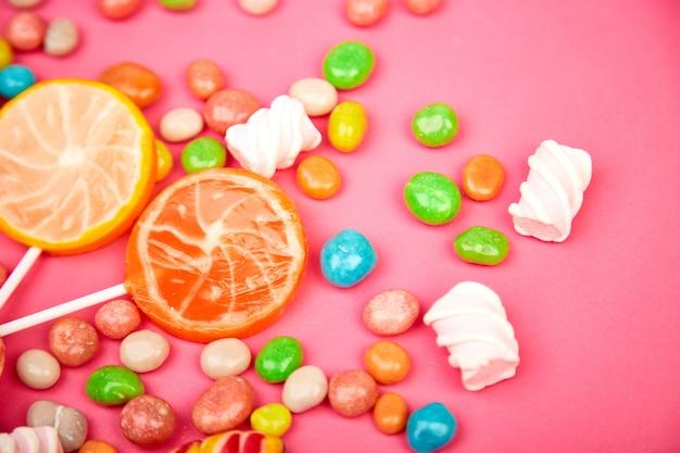 Caramelle colorate, gelatina, lecca-lecca su stecca, spargimento di dolci multicolori