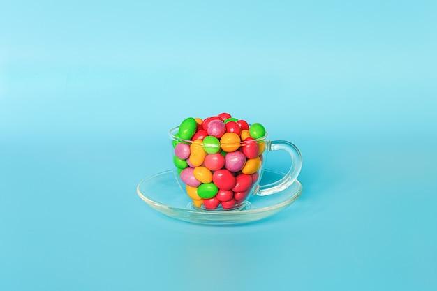 Caramelle colorate smaltate. tazza di vetro sul piattino pieno di cioccolatini colorati a forma di bottone