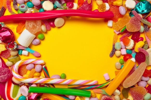 Caramelle colorate su sfondo giallo con copyspace