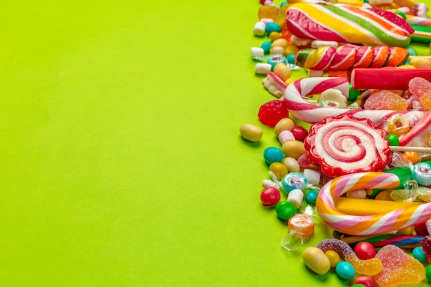 Caramelle colorate su sfondo verde