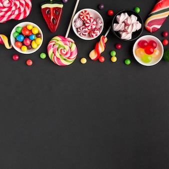 Caramelle deliziose sulla tavola nera con lo spazio della copia