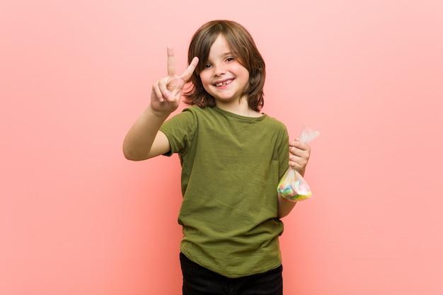 Caramelle della tenuta del ragazzino che mostrano numero due con le dita
